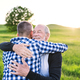 Free Download An adult hipster son with senior father on a walk in nature at sunset, hugging. Nulled