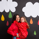Free Download A small girl with her mother on a black background with clouds and raindrops. Nulled