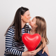 Free Download A small girl and her mother holding a red heart in a studio. Nulled