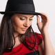 Free Download A close-up of a young beautiful woman with black hat in a studio. Nulled