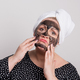 Free Download A sad overweight woman with black facial mask on her face in a studio. Nulled