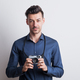 Free Download Portrait of a young man in a studio with a camera. Copy space. Nulled