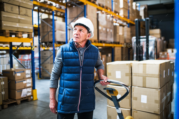 Senior male warehouse worker pulling a pallet truck. - Stock Photo - Images