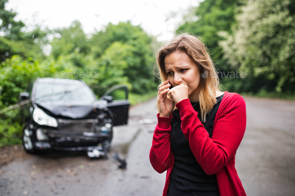 A young woman with smartphone by the damaged car after a car accident, making a phone call. - Stock Photo - Images
