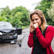 A young woman with smartphone by the damaged car after a car accident, making a phone call. - PhotoDune Item for Sale