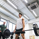 Fit young man with a personal trainer in gym working out, lifting barbell. - PhotoDune Item for Sale
