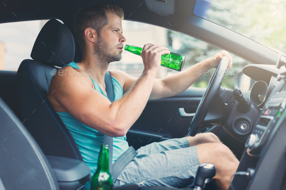 Drunk driver behind the steering wheel of a car - Stock Photo - Images