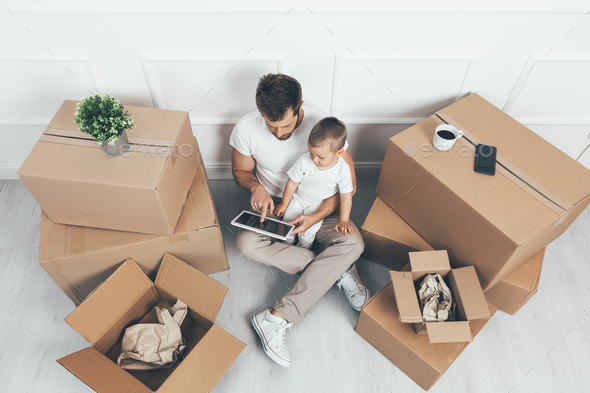 Top view. Father and son moving into a new home - Stock Photo - Images