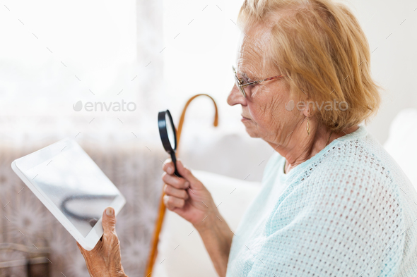 Elderly woman with glasses and loupe using a digital tablet - Stock Photo - Images