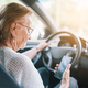 Elderly woman behind the steering wheel using her phone - PhotoDune Item for Sale