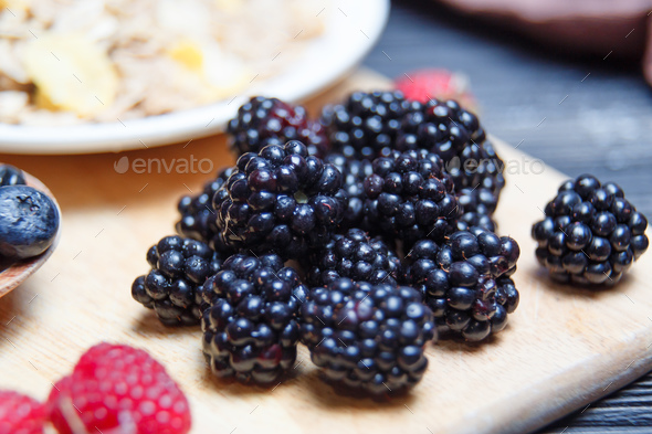Ripe and sweet blackberries in bowls on wooden table - Stock Photo - Images