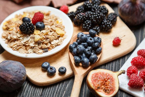 Healthy breakfast set. Muesli and berries on dark rustic background - Stock Photo - Images