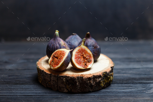 sliced fig fruits on a wooden board - Stock Photo - Images