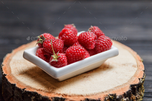 Fresh raspberry in a wooden plate - Stock Photo - Images