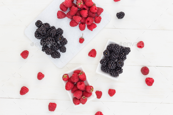 raspberries and blackberries white wooden background - Stock Photo - Images