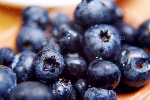 Fresh blueberry with drops of water in wooden bowl. Top view. Concept of healthy and dieting eating - Stock Photo - Images