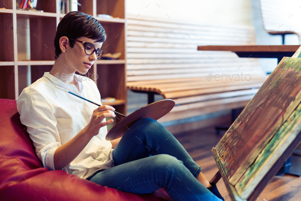 Creative female artist painting new picture - Stock Photo - Images