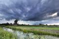 dark shower clouds over Dutch windmill - PhotoDune Item for Sale