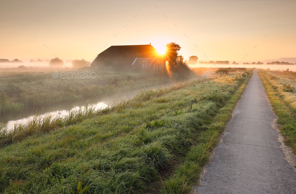 cycling path by farmhouse on misty sunrise - Stock Photo - Images