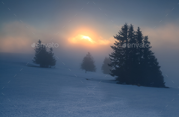 foggy sunrise on snowy mountain top - Stock Photo - Images