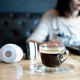Coffee cup on the front desk with people using laptop. - PhotoDune Item for Sale