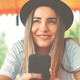 Young hipster girl in trendy hat holding smartphone in hands smi - PhotoDune Item for Sale
