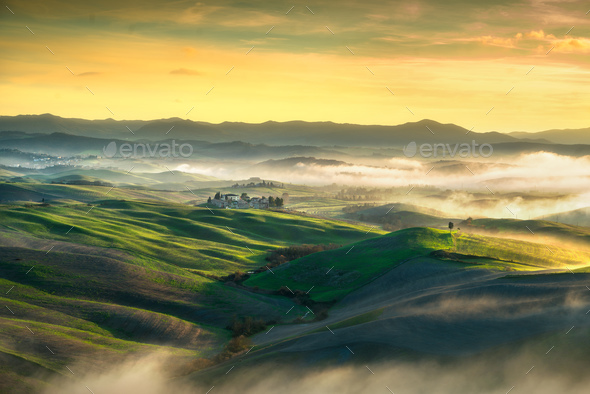 Volterra foggy panorama, rolling hills and green fields on sunse - Stock Photo - Images