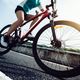 Woman cyclist riding Mountain Bike on highway - PhotoDune Item for Sale