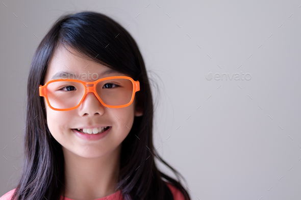 Portrait of Asian teenager with big orange glasses - Stock Photo - Images