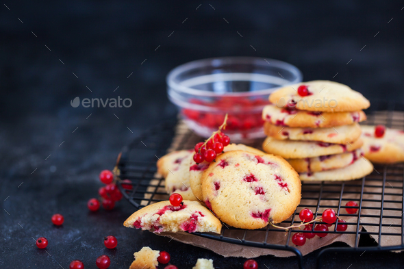 Fresh homemade cookies with red currants on dark background - Stock Photo - Images