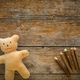 Adorable teddy bear and colored pencils on wooden table. Space for text - PhotoDune Item for Sale