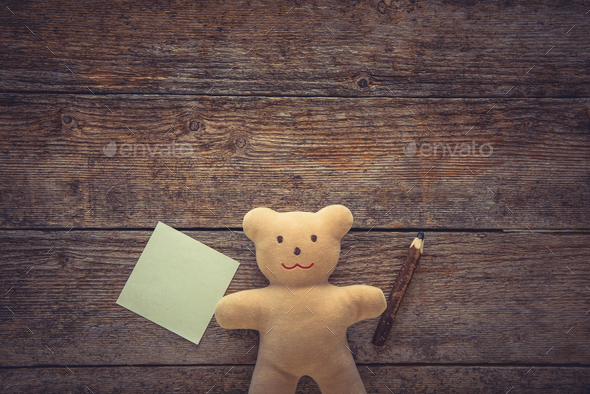 Adorable teddy bear holding sticky note and pencil on wooden table. Space for text - Stock Photo - Images