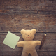 Adorable teddy bear holding sticky note and pencil on wooden table. Space for text - PhotoDune Item for Sale