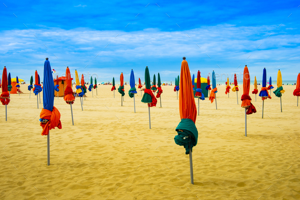 Lots of colorful closed umbrellas on the sunny summer beach with yellow sand - Stock Photo - Images