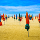 Lots of colorful closed umbrellas on the sunny summer beach with yellow sand - PhotoDune Item for Sale