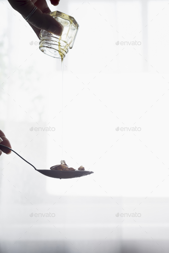 In the hands of the glass jar with honey pours out into a spoon over light window - Stock Photo - Images