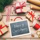 Christmas gift boxes wrapping and a blackboard on wooden background, merry christmas text, top view - PhotoDune Item for Sale