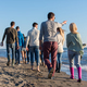 Group of friends running on beach during autumn day - PhotoDune Item for Sale