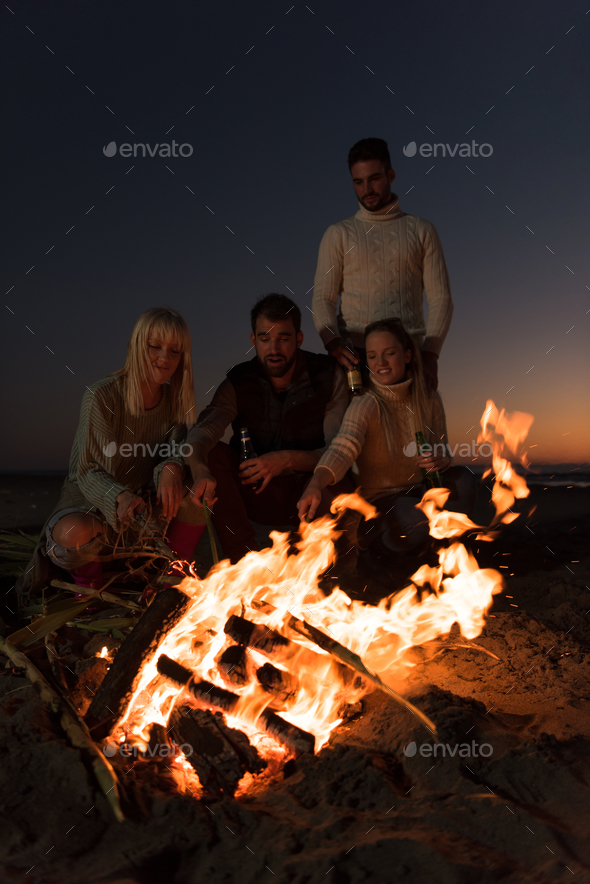 Friends having fun at beach on autumn day - Stock Photo - Images