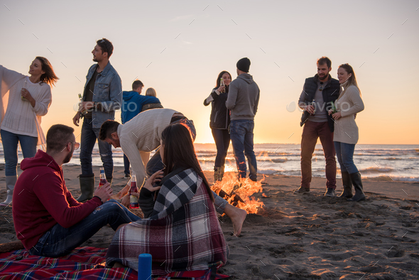 Couple enjoying with friends at sunset on the beach - Stock Photo - Images