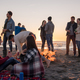 Couple enjoying with friends at sunset on the beach - PhotoDune Item for Sale