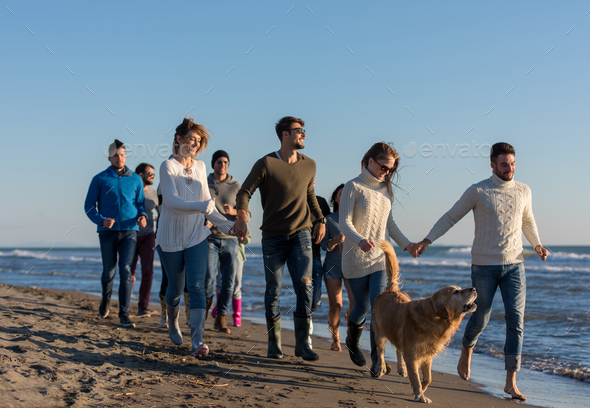 Group of friends running on beach during autumn day - Stock Photo - Images