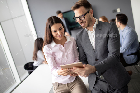 Happy young business colleagues in modern office - Stock Photo - Images