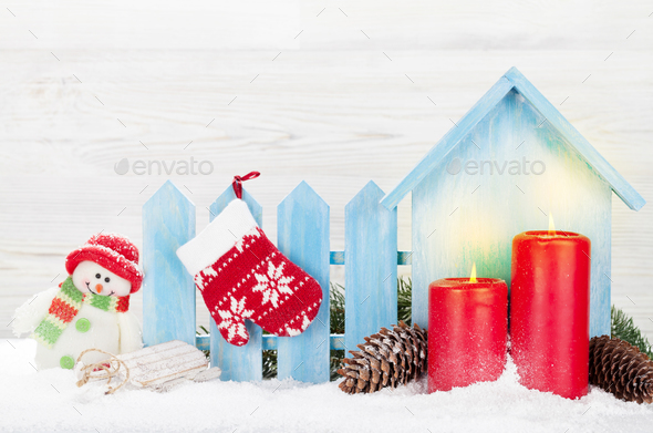 Christmas snowman toy, candles and fir tree branch - Stock Photo - Images