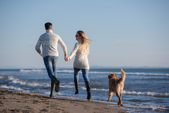 couple with dog having fun on beach on autmun day - Stock Photo - Images