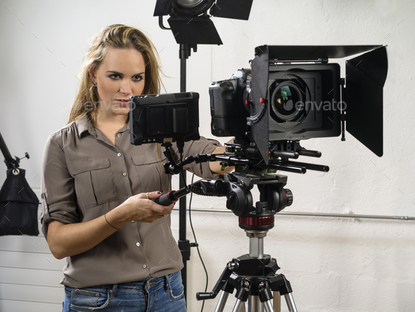 Beautiful woman operating a video camera rig - Stock Photo - Images