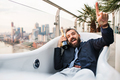 Businessman lying in empty jacuzzi, London view panorama in the background. - PhotoDune Item for Sale