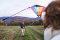 Carefree senior couple flying a kite in an autumn nature. - PhotoDune Item for Sale