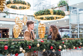A young couple looking at each other in shopping center at Christmas. - PhotoDune Item for Sale