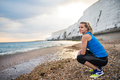 Young sporty woman runner with earphones resting on the beach outside. - PhotoDune Item for Sale